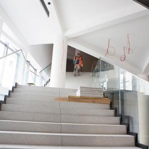 Pracownik w pomarańczowej kamizelce schodzi po jasnych schodach.