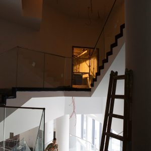 Widok ze schodów na otwarte drzwi i schody.