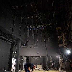 Wysokie pomieszczenie o ciemnych ścianach. Z sufitu zwisają kable. Ubrany w niebieski kombinezon pracownik pochyla się pracując przy budowie podłogi.