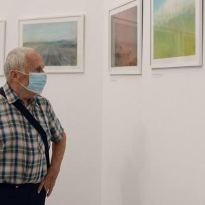 Starszy mężczyzna w kraciastej koszuli ogląda obrazy zawieszone na ścianie.