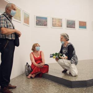 Troje ludzi. Po lewej stronie widać stojącego starszego mężczyznę, po środku kobieta w czerwonej sukni siedzi na stopniu, po prawej kuca kobieta, trzymająca w ręku żółtą różę.