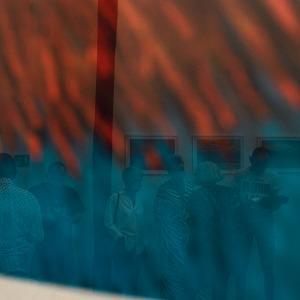 Czerwono-niebieski fragment obrazu, w którym odbija się wnętrze sali wystawowej.