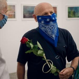 Artysta rozmawia z dwojgiem ludzi. Ma zawieszoną na twarzy niebieską chustę z białym wzorem.