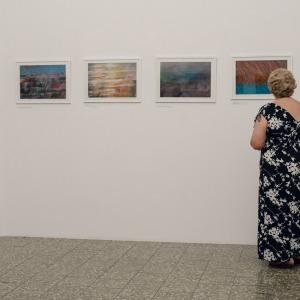 Kobieta w czarnej sukni z białymi elementami stoi tyłem do obiektywu. Ogląda obrazy zawieszone na ścianie.