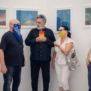 Artysta prowadzi rozmowę z uczestnikami wystawy.