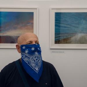 Stefan Rusin z niebieską chustą w białe wzory. W tle widać jego obrazy wykonane suchymi pastelami. W obu przeważa kolor niebieski.