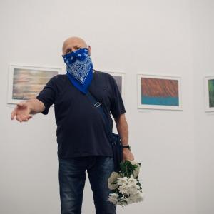 Stefan Rusin na tle swoich obrazów zawieszonych na ścianie. W lewej dłoni trzyma bukiet białych kwiatów.
