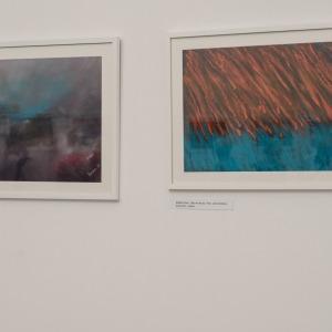 Dwa zawieszone na ścianie obrazy. Po lewej ciemne motywy z elementem błękitu. Obraz po prawej stronie tworzą czerwono-błękitne wstęgi.