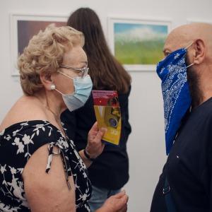 Kobieta w czarnej sukni z białymi elementami rozmawia z malarzem.