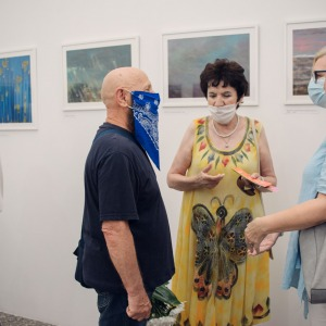 Andrzej Rusin prowadzi rozmowę z dwiema uczestniczkami wystawy.