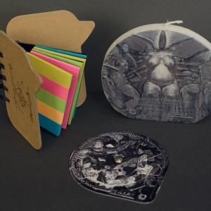 Notes z nadrukowanym podpisem mistrza Starowieyskiego, obracany puzzel dla dorosłych z nadrukiem ukrytego fragmentu pracy oraz świeczka z główną postacią obrazu.