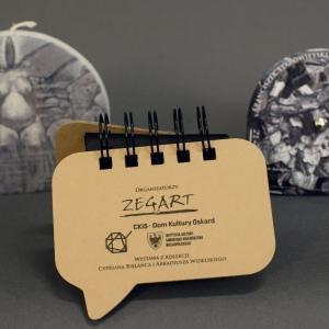 Świeczka z główną postacią obrazu, notes z nadrukowanym podpisem mistrza Starowieyskiego oraz obracany puzzel dla dorosłych z nadrukiem ukrytego fragmentu pracy.