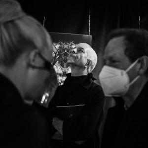 Na pierwszym rozmytym planie rozmawia ze sobą dwoje ludzi. W tle pomiędzy nimi Tadeusz Topolski stoi z uniesioną głową. Zdjęcie czarno-białe.