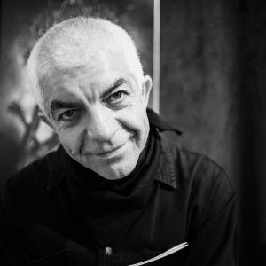Tadeusz Topolski spogląda w obiektyw. Zdjęcie czarno-białe.