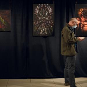 Trzy fotografie zawieszone pod sufitem. Za nimi czarna tkanina. Przed nimi bokiem stoi pochylony nad notesem mężczyzna w zielonej kurtce.
