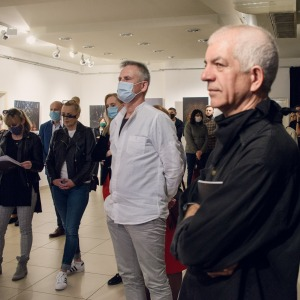 Na pierwszym planie po prawej stronie Tadeusz Topolski stoi bokiem do obiektywu. W tle uczestnicy wystawy.