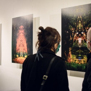 Kobieta i mężczyzna stoją tyłem do obiektywu. Przyglądają się fotografii zawieszonej na białej ścianie. Zdjęcie nasycone jest czernią i zielenią.