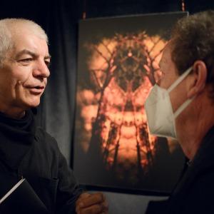Tadeusz Topolski rozmawia z mężczyzną w białej maseczce. W tle zawieszone pod sufitem zdjęcie artysty. Przedstawia ono czarne konary drzew otoczone czerwonymi obłokami.