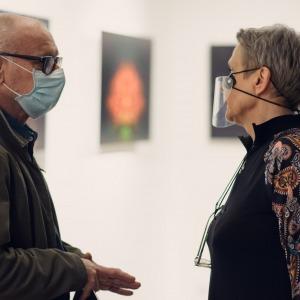 Krystyna Mikołajczak rozmawia z mężczyzną w niebieskiej maseczce i okularach.