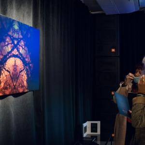 Po lewej stronie zawieszone pod sufitem zdjęcie skąpane w niebieskim świetle. Za nim czarna tkanina. Po prawej grupa kobiet. Jedna z nich spogląda w obiektyw.