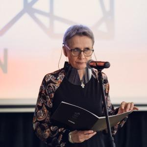Krystyna Mikołajczak stoi przed mikrofonem. W dłoniach trzyma teczkę. Za nią widać slajd z logiem Centrum Kultury i Sztuki w Koninie.