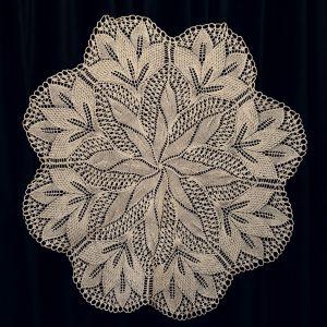 Beżowy haft przedstawiający kwiat o ośmiu płatkach.