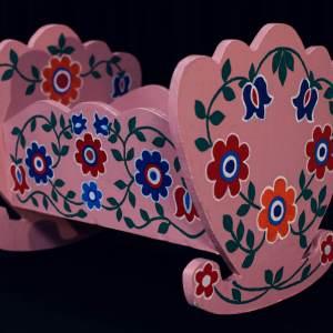 Mała drewniana różowa kołyska ozdobiona kwiatowym malowidłem.