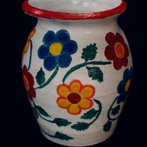 Biały wazon z czerwoną obwódką u szczytu. Ozdobiony kwiatami w kolorach żółtym, niebieskim i czerwonym.