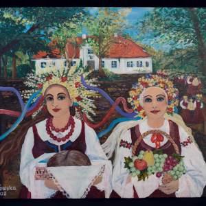 Obraz przedstawiający dwie młode kobiety w strojach ludowych. Kobieta po lewej stronie trzyma tacę z bochenkiem chleba. Natomiast pani po prawej kosz owoców. Za nimi widać biały dworek z czerwonym dachem.