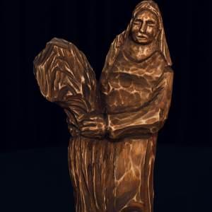 Drewniana figurka przysadzistej kobiety trzymającej zboże.
