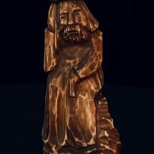 Drewniana figurka starszego mężczyzny z brodą oraz czapką na głowie. Ma zamyśloną minę.
