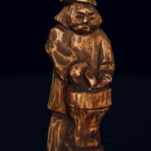 Drewniana figurka mężczyzny w kapeluszu. Kłuje żelazo.