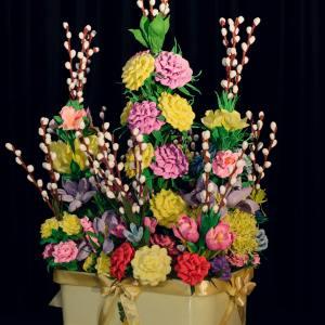 Stroik wielkanocny złożony z różnokolorowych kwiatów. Kwiaty wykonane są z bibuł. Pomiędzy umieszczone bazie.