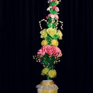 Podłużny bukiet różnokolorowych kwiatów wykonanych z bibuły. Włożony w dzbanek ozdobiony motywem żonkili.