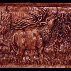 Lakierowana brązowa płaskorzeźba przedstawiająca jelenia.