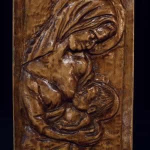 Lakierowana jasnobrązowa płaskorzeźba przedstawiająca Matkę Boską, która karmi Dzieciątko.