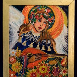 Niewielkich rozmiarów obraz oprawiony drewnianą ramką.  Przedstawia złotowłosą anielicę z pomarańczową mandoliną. Wokół głowy ma kwiecistą aureolę otoczoną pomarańczowym kręgiem.  Po bokach widać białe skrzydła.