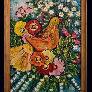 Niewielkich rozmiarów obraz oprawiony drewnianą ramką. Przedstawia pomarańczowo-żółtego ptaka pośród różnego koloru kwiatów.