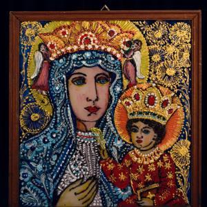 Obraz przedstawiający Matkę Boską z Dzieciątkiem. Po bokach głowy kobiety znajdują się małe postaci aniołów.  Granatowe tło ozdobione jest złotymi kwiatami.  Obraz oprawiono drewnianą ramą.