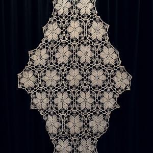 Ręcznie wyszywana serweta w kształcie wydłużonego rombu.