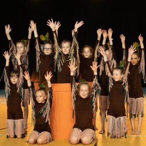 Grupa 10 dziewczynek w brązowych strojach z frędzlami unosi w górę ręce.