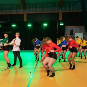 Grupa dziewczyn w kolorowych topach i czarnych spodenkach. Wśród nich chłopak w ciemnych spodniach, białej koszuli, czerwonym krawacie i okularach.