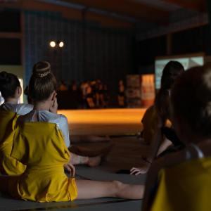 Grupa dziewczynek w żółtych strojach siedzi tyłem na podłodze. Włosy mają upięte w koki. Część z nich siedzi w szpagacie tureckim.