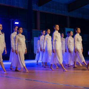 Grupa dziewczyn w białych strojach. Stąpają wyciągając w przód prawe nogi.