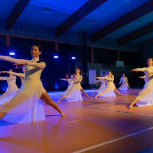 Grupa dziewczyn w białych strojach. Stoją w rozkroku z prawą nogą i ramionami wyciągniętymi w przód.