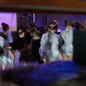 Zdjęcie zza rusztowania. Grupa dziewczynek w strojach sów - białe i brązowe tiule i piórka. Na oczach maseczki.