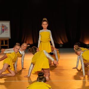 Dziewczynki w żółtych strojach klęczą na lewym kolanie. Pośrodku stojąca przodem wyprostowana koleżanka.