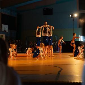 Nieostre plecy obserwujących. Pośrodku kadru tańczcące dziewczynki w biało-granatowych strojach z gwiazdkami. Część z nich kuca, część podnosi nogi, a część unosi koleżankę w górę.
