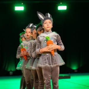 Dzieci w strojach zajączków stoją w rzędzie. W dłoniach trzymają marchewki.