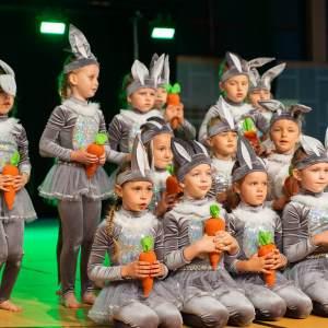 Dzieci w strojach zajączków pozują do zdjęcia. Mają na sobie szare getry, tiulowe szare spódniczki, długie uszy na głowie, a w dłoniach marchewki.
